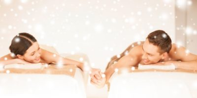 health and beauty, love, romance concept - couple in spa salon drinking champagne